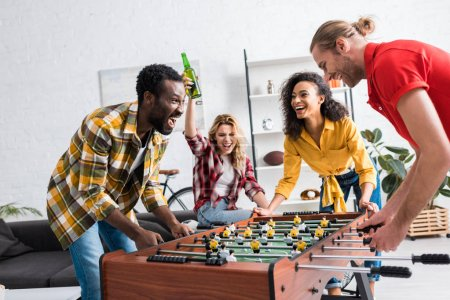 Photo for Four happy and joyful multiethnic friends playing table football in living room - Royalty Free Image
