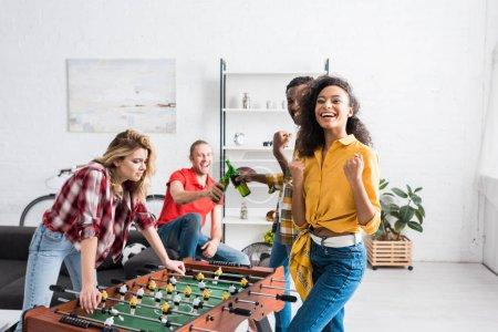 Foto de Happy and smiling multiethnic men and women playing table football in living room at home - Imagen libre de derechos