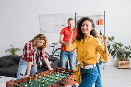 Foto de Young and happy multiethnic friends having joyful time together while playing table football - Imagen libre de derechos