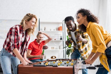Foto de Four happy multicultural friends talking and laughing over table football game in living room - Imagen libre de derechos