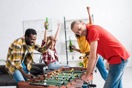 Photo for Happy multicultural  friends drinking beer, celebrating and playing table football in living room - Royalty Free Image