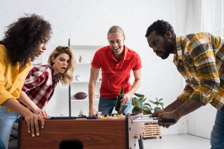 Photo for Four excited multicultural friends playing table football in living room at home - Royalty Free Image