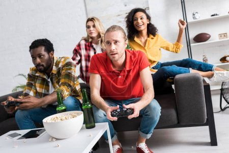 Foto de Enfoque selectivo de los hombres multiculturales jugando videojuego cerca de las niñas en casa - Imagen libre de derechos