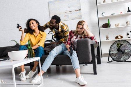 Foto de Vista de ángulo bajo de chica molesta sentado cerca de amigos afroamericanos felices en la sala de estar - Imagen libre de derechos