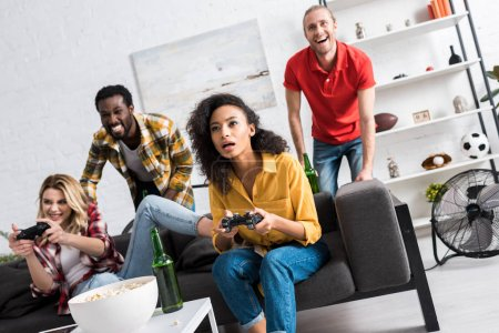 Photo for Low angle view of happy multicultural girls playing video game near friends - Royalty Free Image