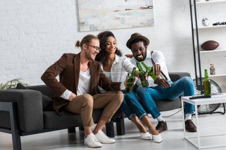 Photo for Cheerful multicultural men toasting with african american girl in living room - Royalty Free Image