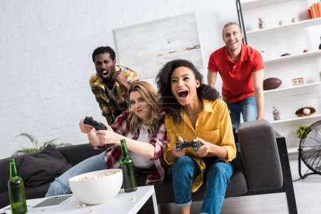 Photo pour Excited multicultural girls playing video game near men in living room - image libre de droit