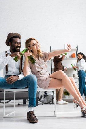 Foto de Low angle view of happy girl taking selfie with cheerful african american man holding bottle of beer - Imagen libre de derechos