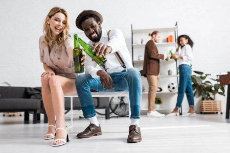 Photo pour Foyer sélectif de la fille heureuse riant et clinking des bouteilles de bière avec l'homme américain africain gai - image libre de droit