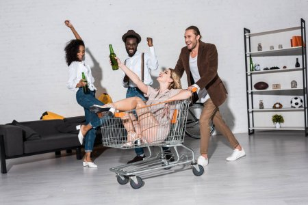 Foto de Happy stylish girl riding in shopping cart near multicultural friends holding bottles of beer - Imagen libre de derechos
