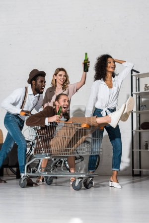 Photo for Cheerful man riding in shopping card and holding bottle near happy multicultural friends - Royalty Free Image