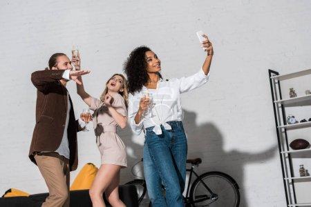 Foto de Vista de ángulo bajo de atractiva chica afroamericana tomando selfie con amigos sosteniendo copas de champán - Imagen libre de derechos