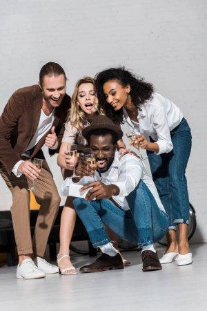 Foto de Vista de ángulo bajo de hombre afroamericano feliz tomando selfie con amigos sosteniendo copas de champán - Imagen libre de derechos