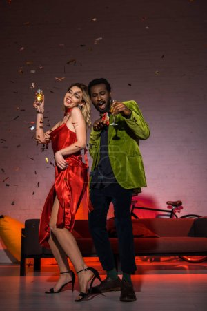 Photo for Low angle view of happy african american man standing with blonde woman in red dress and holding champagne glass - Royalty Free Image