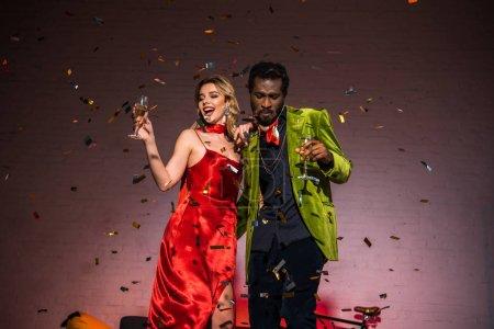 Photo pour Vue à angle bas de l'homme afro-américain debout avec une femme blonde en robe rouge et tenant verre de champagne - image libre de droit