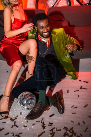 Photo for Cropped view of woman in red dress sitting near african american man with champagne glass - Royalty Free Image