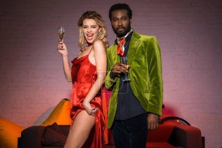 Photo pour Vue basse d'angle de fille blonde excitée retenant le verre de champagne près de l'homme américain africain - image libre de droit