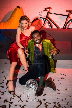 Photo for Young blonde woman in red dress sitting near african american man with champagne glass - Royalty Free Image