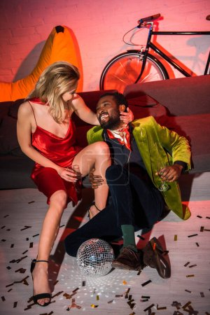 Photo for Young blonde woman in red dress sitting with african american man in night club - Royalty Free Image