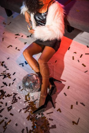 Photo for Cropped view of african american girl holding champagne glass while sitting on floor with confetti - Royalty Free Image