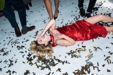 Photo pour Fille blonde attirante et ivre dans la robe rouge se trouvant sur l'étage avec des confettis près des amis - image libre de droit