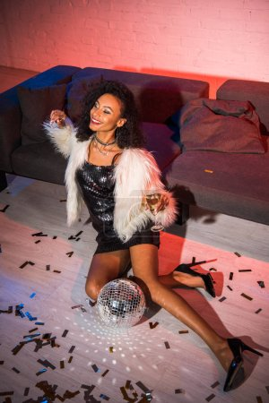Photo for Attractive african american girl holding champagne glass while sitting on floor near confetti - Royalty Free Image