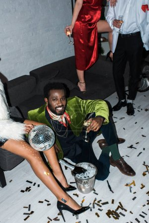 Photo for Overhead view of african american man holding champagne glass while sitting on floor near friends - Royalty Free Image