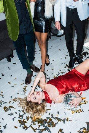 Foto de Chica rubia atractiva y borracha con vestido rojo acostado en el suelo con confeti y sosteniendo la bola de discoteca cerca de amigos - Imagen libre de derechos