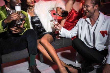 Photo pour Vue recadrée de femme américaine africaine retenant la bouteille près du verre de champagne tout en s'asseyant près des amis multiculturels - image libre de droit