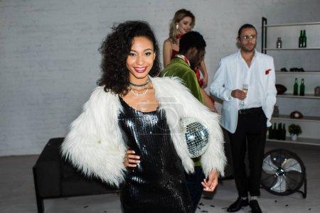 Photo pour Foyer sélectif de la fille américaine africaine retenant la boule de disco tout en restant près des amis - image libre de droit