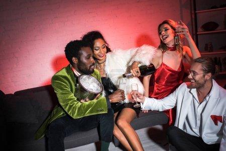 Photo pour Femme américaine africaine retenant la bouteille près du verre de champagne tout en s'asseyant près des amis multiculturels - image libre de droit