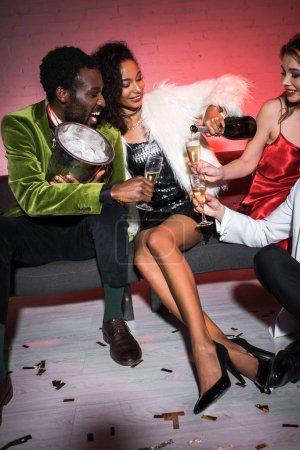 Photo pour Fille américaine africaine retenant la bouteille près des glaces de champagne tout en s'asseyant près des amis multiculturels - image libre de droit