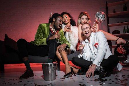 Photo pour Vue basse d'angle de femme attirante retenant la boule de disco tout en s'asseyant près des amis multiculturels - image libre de droit