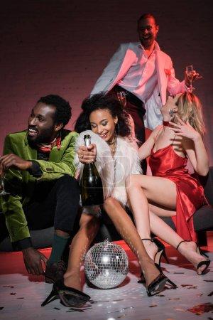 Photo pour Vue basse d'angle de la femme américaine africaine retenant la bouteille tout en s'asseyant avec des amis multiculturels dans le club - image libre de droit