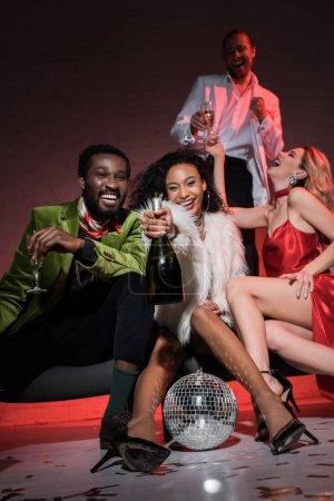 Foto de Vista de ángulo bajo de hombre afroamericano sosteniendo copa de champán mientras se sienta con amigos multiculturales - Imagen libre de derechos