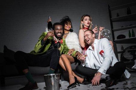Foto de Vista de ángulo bajo de hombre afroamericano sosteniendo copa de champán mientras se sienta cerca de amigos multiculturales - Imagen libre de derechos