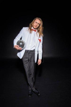 Foto de Hombre guapo en gafas sosteniendo bola de discoteca mientras que de pie con las piernas cruzadas en negro - Imagen libre de derechos