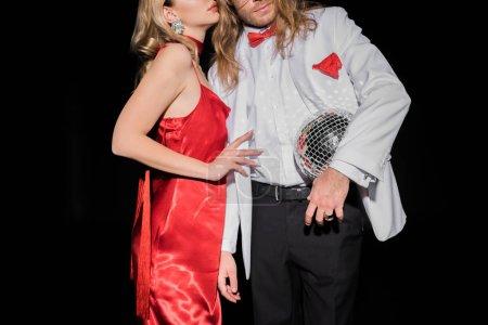 Foto de Vista recortada de chica rubia sosteniendo bola de discoteca brillante y de pie cerca del hombre aislado en negro - Imagen libre de derechos
