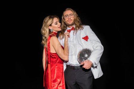 Foto de Mujer atractiva en vestido rojo tocando pajarita de hombre en gafas con bola de discoteca aislada en negro - Imagen libre de derechos