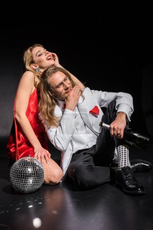 Foto de Chica rubia atractiva cerca del hombre sosteniendo la botella mientras se sienta cerca de la bola de discoteca en negro - Imagen libre de derechos