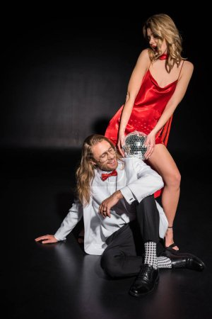 Photo for Surprised girl holding disco ball near man in glasses sitting on black - Royalty Free Image