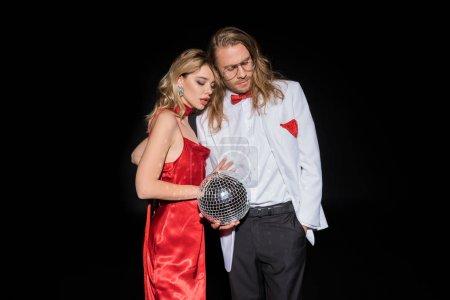 Foto de Hermosa chica rubia en vestido rojo sosteniendo bola de discoteca cerca del hombre en gafas aisladas en negro - Imagen libre de derechos