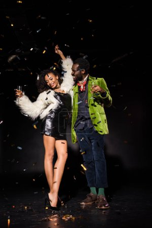 Photo for Cheerful african american man and woman holding champagne glasses near falling confetti on black - Royalty Free Image