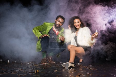 Photo for African american man and woman holding champagne glasses while sitting near confetti on black with smoke - Royalty Free Image