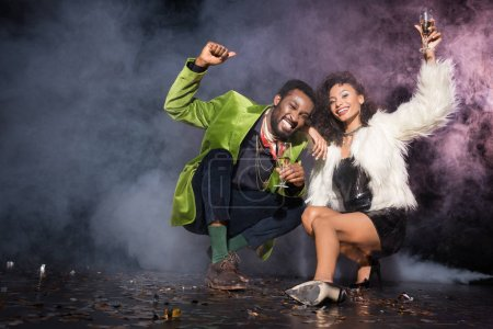 Photo for Happy african american man and woman holding champagne glasses while sitting near confetti on black with smoke - Royalty Free Image