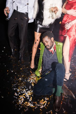 Photo for Handsome and drunk african american man lying on floor with shiny confetti near friends on black - Royalty Free Image