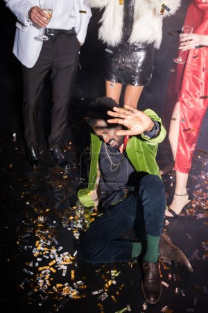 Photo for Drunk african american man with closed eyes gesturing while lying on floor with shiny confetti near friends on black - Royalty Free Image