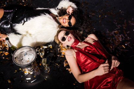 Photo for Overhead view of blonde girl lying on floor with confetti near african american friend in sunglasses on black - Royalty Free Image