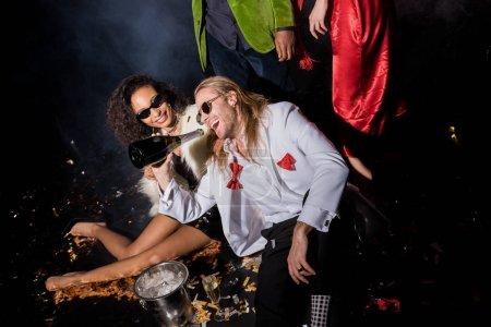 Photo pour Heureux afro-américain femme près beau homme dans des lunettes de soleil boire de la bouteille près de confettis et amis sur noir - image libre de droit