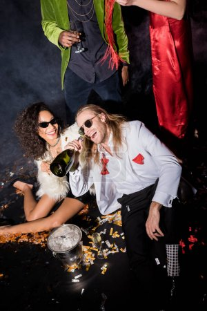 Photo for African american woman near happy man in sunglasses with bottle of champagne near confetti and friends on black - Royalty Free Image